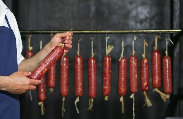 Массивная колбаса производится и развешивается внутри фабрики