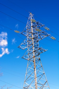 Mast high-voltage line against the blue sky