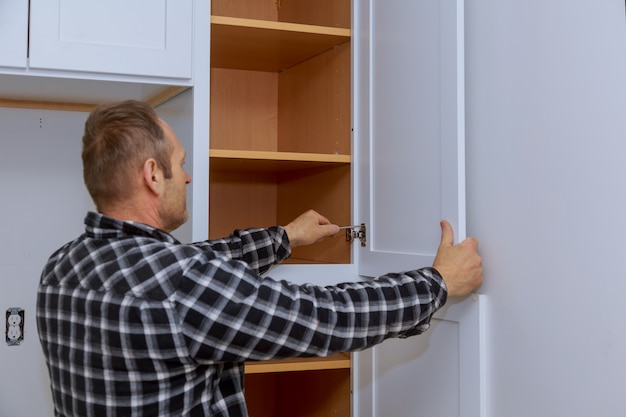 Master adjusts fixing the hinge of the kitchen cabinet door with screwdriver.