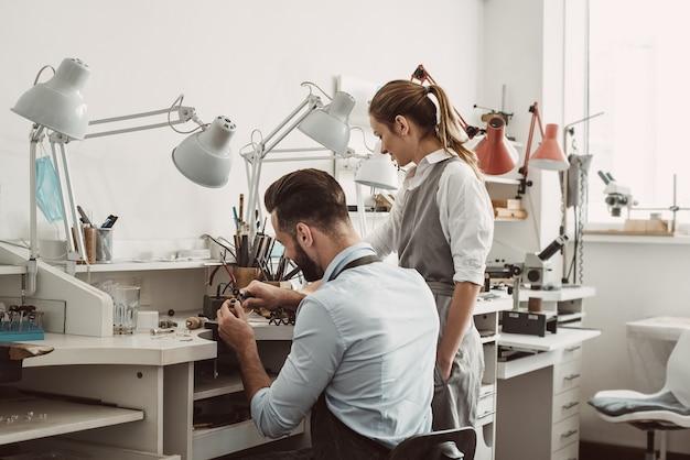 마스터와 견습생. 젊은 남성 조수와 여성 보석상이 보석 제작 워크샵에서 함께 일하고 있습니다. 사업