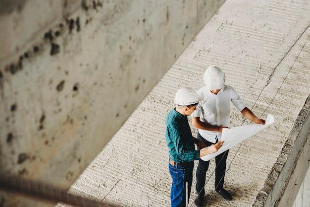 마스터와 arhitect가 작업을 개선하기 위해 뜨겁고 건설중인 건물에서 작업 속도를 높이는 방법에 대해 이야기합니다.