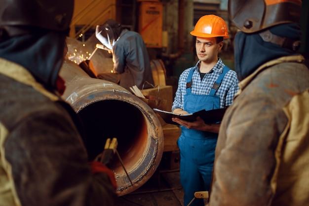 Мастер и бригада сварщиков работают с металлоконструкциями на заводе, сварочное мастерство. металлообрабатывающая промышленность, промышленное производство стали.