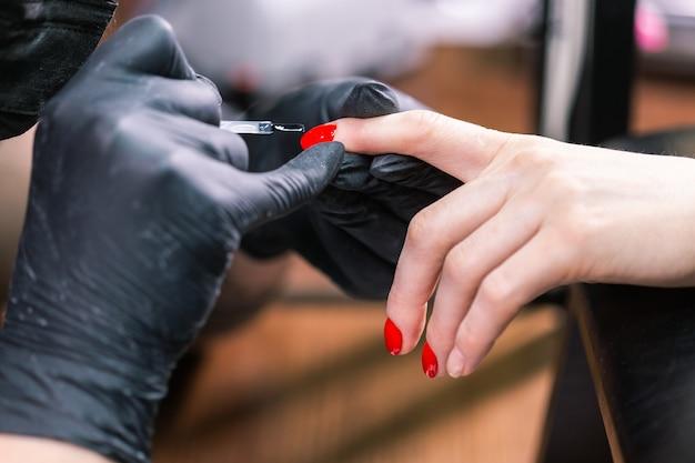 마스터는 매니큐어 살롱에서 손톱 젤에 바니시 그리기를 적용했습니다. 젤 폴란드어 개념.