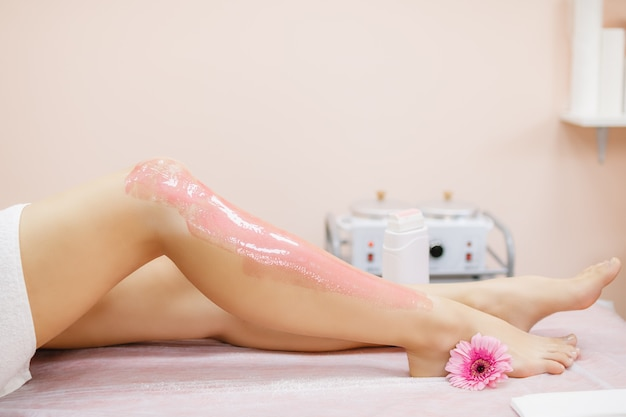 Master applies pink depilatory wax to a young woman's leg for hair removal.