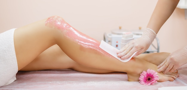 A master applies pink depilatory wax to a young woman's leg for hair removal