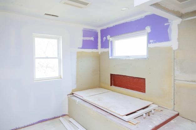 Главная ванная комната с новым строящимся гипсокартоном ванной комнаты, готовым к плитке в новом роскошном доме