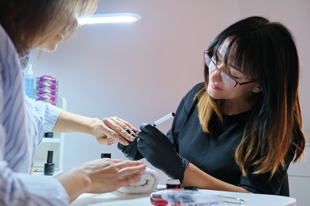 Master beautician painting art design on nails.