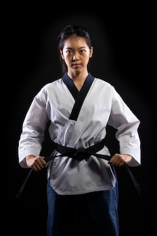 Master black belt taekwondo karate girl who is national athlete young teenager show traditional fighting poses punch in sport uniform dress, black wall isolated, motion blur on foots hands