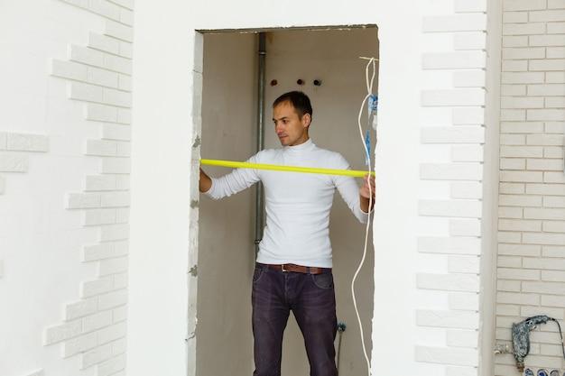 巻尺で白い壁の距離を測定する制服を着たマスタービルダー
