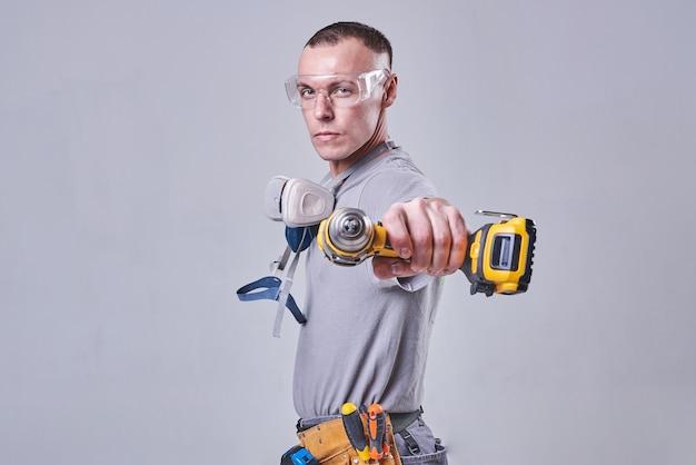 Мастер строительфинишер в рабочей одежде с дрелью-отверткой в руке
