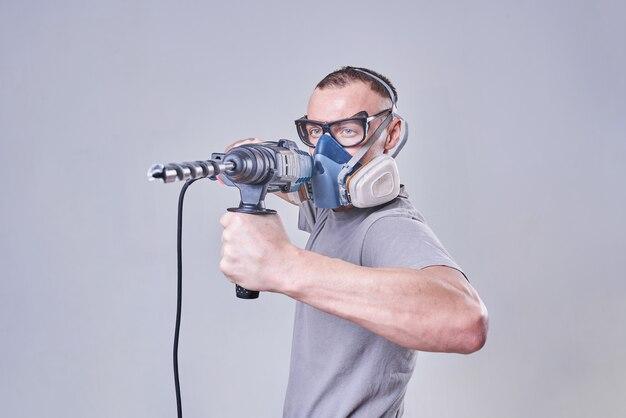 Мастер строительфинишер в спецодежде с перфоратором в руках
