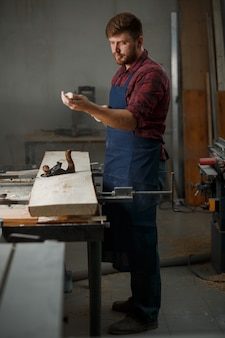 Master carpenter in shirt and apron in the workshop
