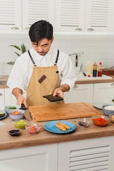 마스터 요리사가 주방 음식 배달에 노리 아시아 요리사와 함께 스시 롤을 만듭니다.