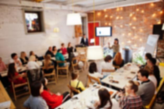 Мастер-класс и концепция обучения. резюмируйте запачканное фото комнаты конференции или семинара с диктором на сцене.