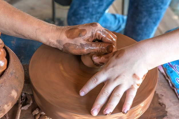 도예 마스터 클래스 도예가가 아이에게 붉은 점토로 요리를 만드는 법을 가르친다