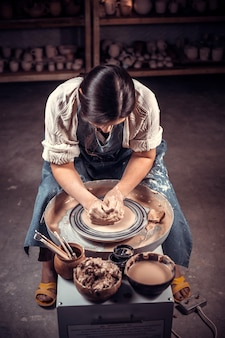 Master class on modeling of clay on a potter's wheel in the pottery workshop.