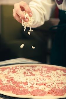 피자 가게에서 피자 요리에 대한 마스터 클래스. 오븐에서 굽기 위해 피자를 준비합니다.