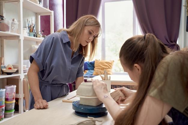 Мастер-класс по изготовлению посуды из глины, одна женщина учит другую на мастер-классе.