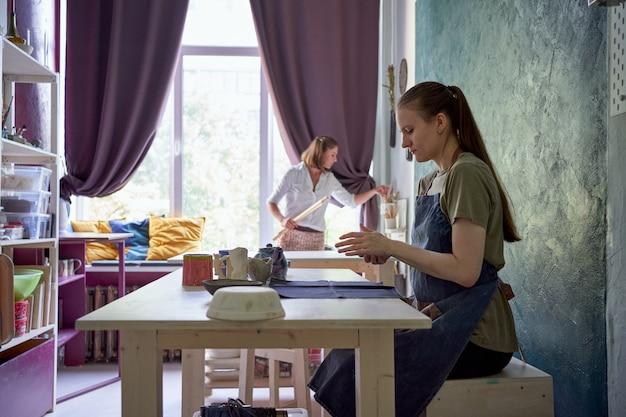 Мастер-класс по изготовлению посуды из глины, одна женщина учит другую