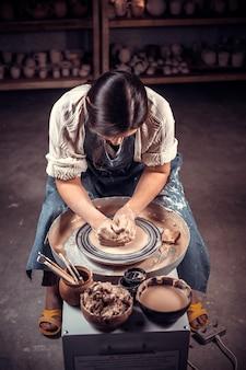 ろくろの粘土のモデリングに関するマスタークラス陶器のワークショップで。