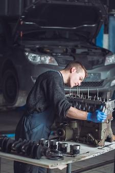 Мастер собирает восстановленный мотор для автомобиля.