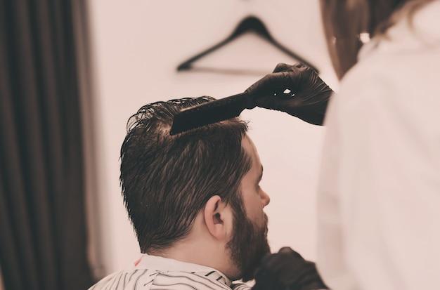 マスターが理髪店で髪の毛とひげをとかす