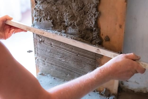 マスターコンクリート労働者は大きなへらでモルタルを水平にします
