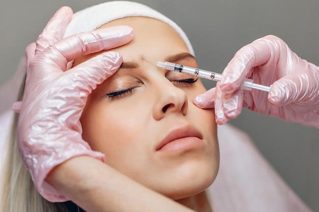 Мастер-косметолог делает уколы антивозрастного ботокса красивой молодой женщине с гладкой кожей.