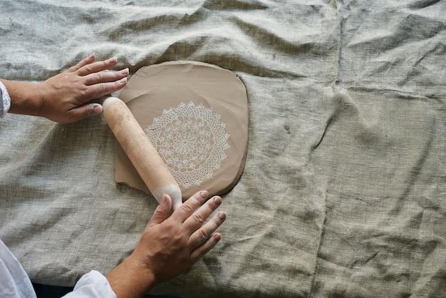 名工がテーブルの上で粘土を転がし、ナプキンの模様を粘土の塊に移します