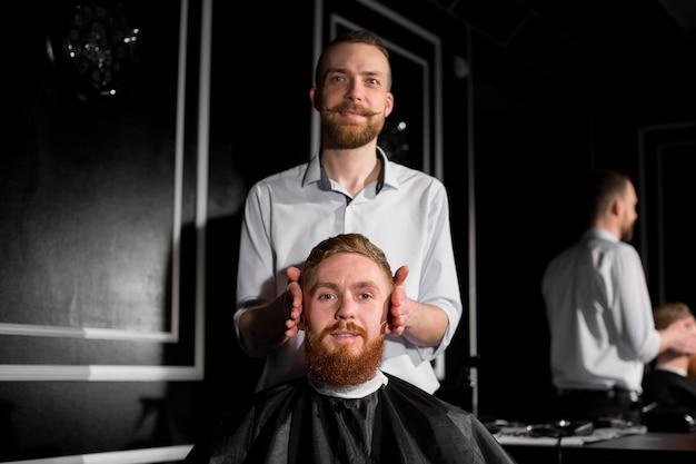 Мастер стрижет волосы и бороду в парикмахерской. парикмахер делает прическу с помощью ножниц и металлической расчески. не доволен работой клиента.