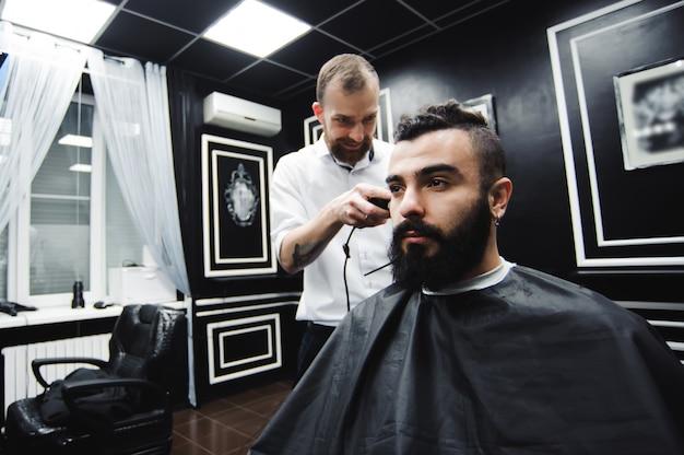 Мастер стрижет волосы и бороду мужчины в парикмахерской, парикмахер делает прическу для молодого человека.