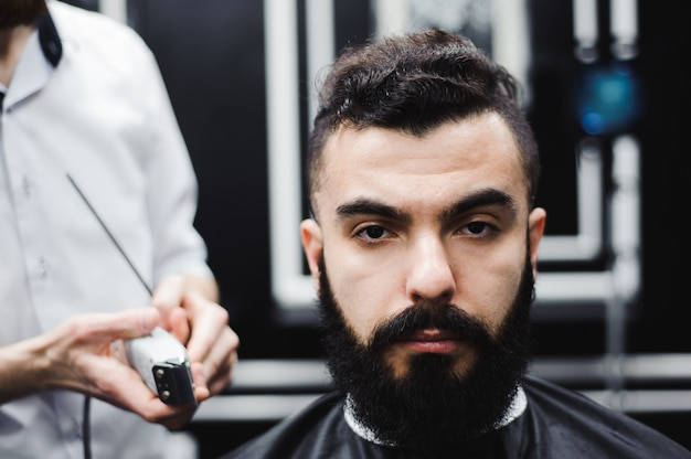 Мастер стрижет волосы и бороду мужчин в парикмахерской, парикмахер