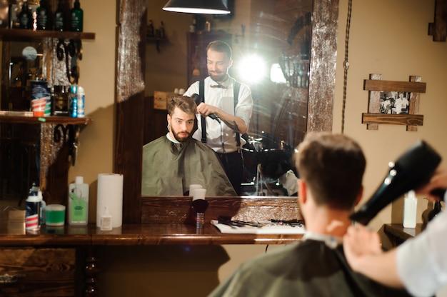 마스터는 이발소에서 남자의 머리카락과 수염을 자릅니다.