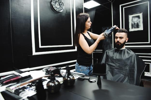 Мастер стрижет волосы и бороду мужчин в парикмахерской