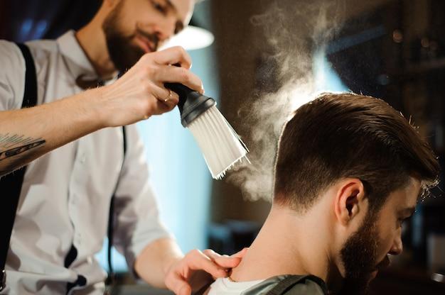 Master cuts hair and beard of men in the barbershop