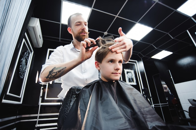 Master cuts hair of a boy in the barbershop, hairdresser makes hairstyle for a boy.