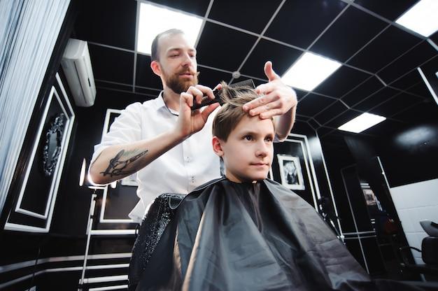 マスターは理髪店で男の子の髪をカットし、美容師は男の子の髪型を作ります。