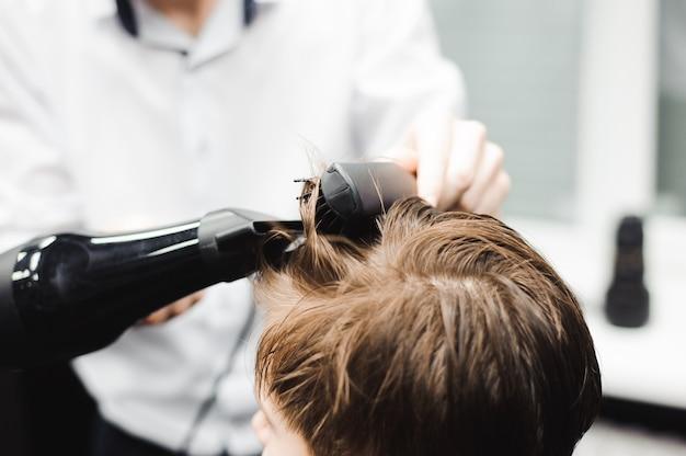 Мастер стрижет волосы мальчика в парикмахерской