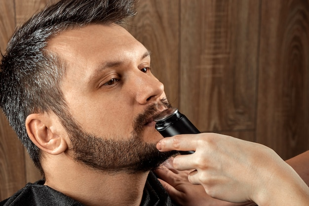 Master cuts nose hair to client with trimmer, close-up. the process at the hairdresser, barbershop. body care, lifestyle, metrosexual.
