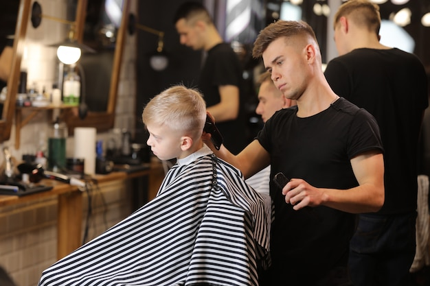 Master cutting hair of a boy in a barbershop