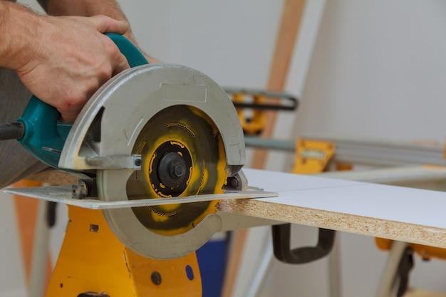 Мастер раскроя ручной электропилой распилил кусок ламинированной полки из дерева в квартире.