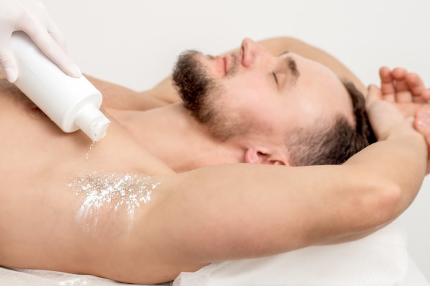 Master depilation pouring talcum powder on armpit