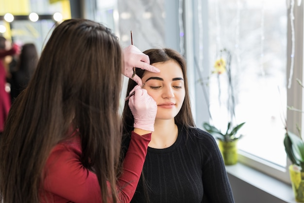 Master doing make-up with wide black eyebrow lines