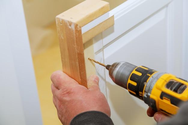 Master drills the cabinet door in the cabinet door