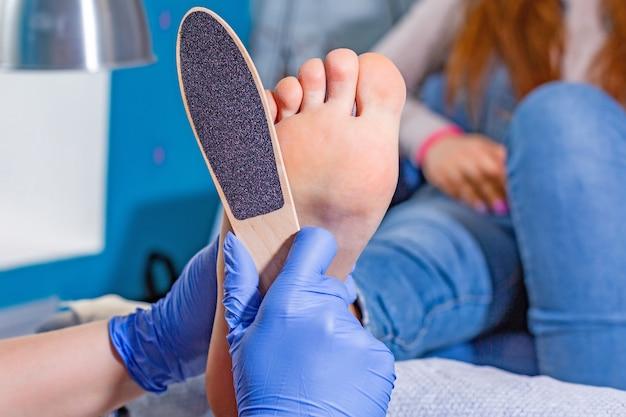 Мастер во время педикюра. процесс профессионального педикюра. волшебник в маске наносит гель на ногти кисточкой. концепция красоты и здоровья