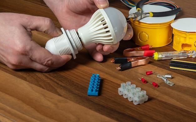 마스터 전기 기술자가 전구를 켭니다. 바탕 화면에 작업자 손 클로즈업