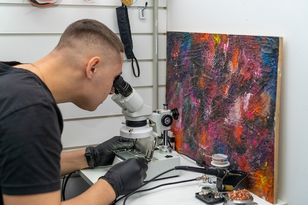 The master examines the microboard through a microscope on a disassembled smartphone