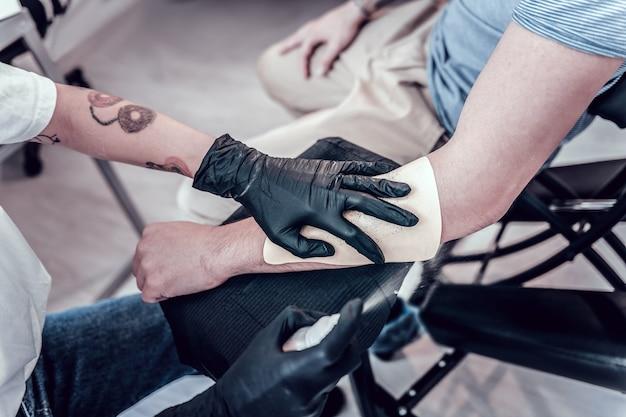マスター接着ステッカー。タトゥーマスターが将来のタトゥーのステッカーに手を置いて、それを近づけます
