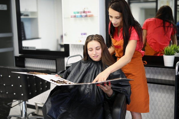 Мастер-парикмахер помогает клиенту выбрать цвет краски для волос.
