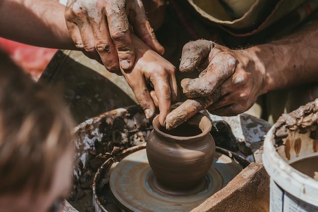 Master handmakes a pot of clay